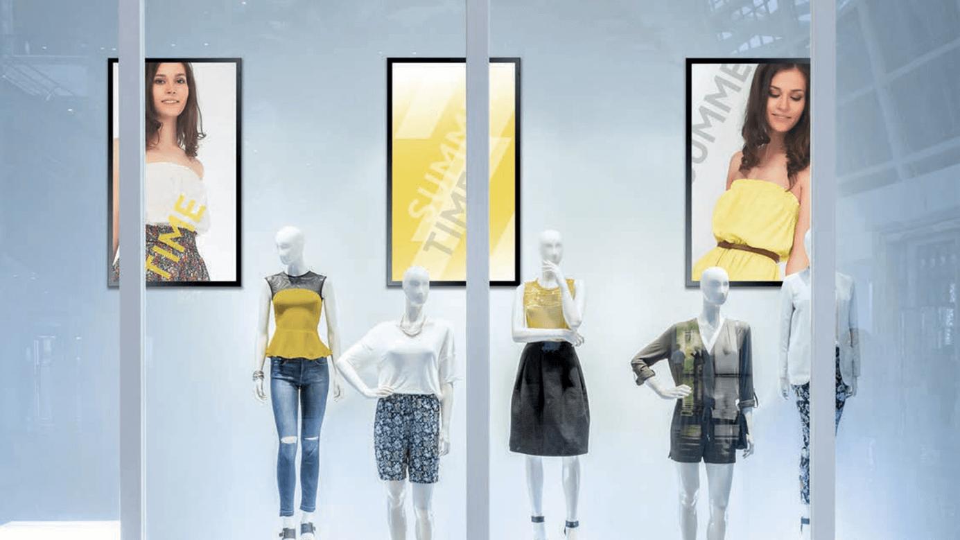 Hochformatige Digital Signage Schaufensterdisplays vor Schaufensterpuppen