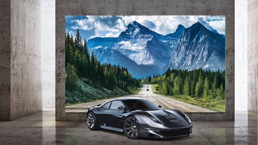 Ein Auto vor einem übergroßen Display mit Naturmotiv