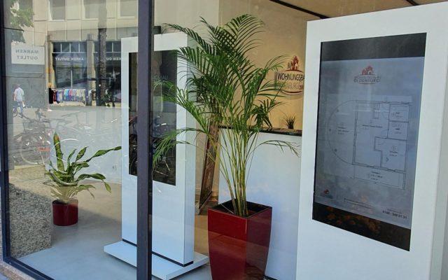 Zwei Digital Signage-Stelen von Kleinhempel im Schaufenster von Wohnungsbau Oldenburg