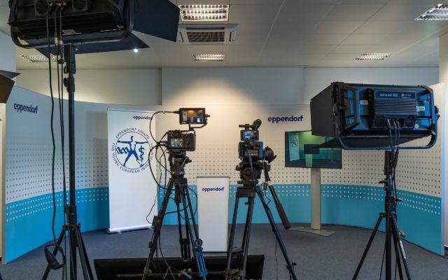 Hintergrundwand mit Logomotiv für Videoproduktionen (mit Kameras im Vordergrund)